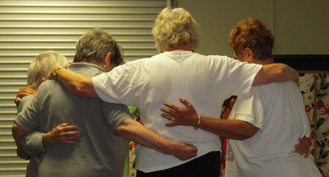 senior women in a group embrace