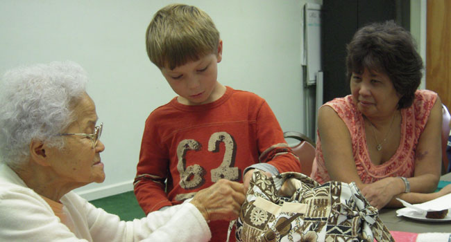 Quilters teaching young boy